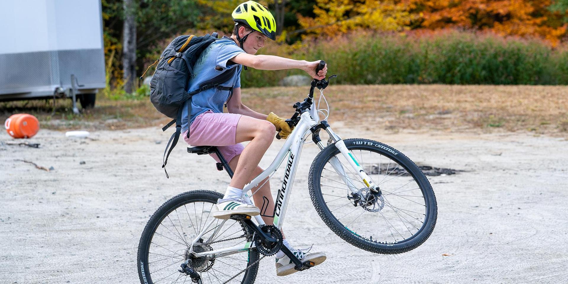 A student pops a wheelie on their mountain bike.
