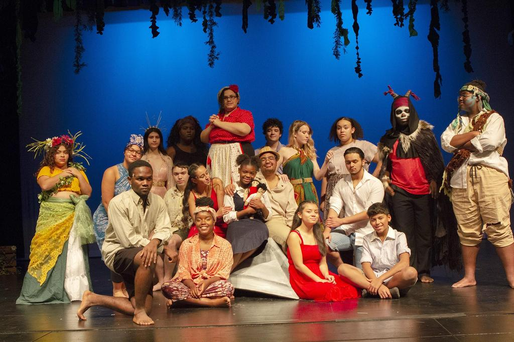 The cast members, in full costume, gather on stage for a group photo