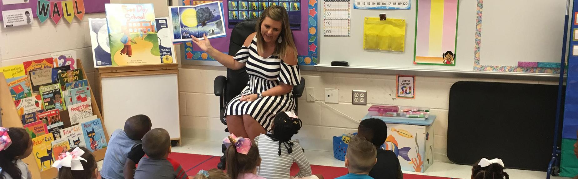 Kindergarten teacher reads to students on the first day of school.