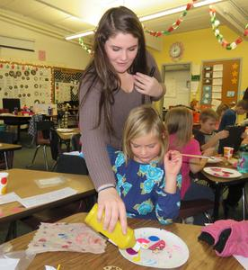 A TKHS student gives some paint to a first grader.