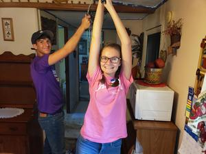 photo of two student volunteers painting the ceiling in a home