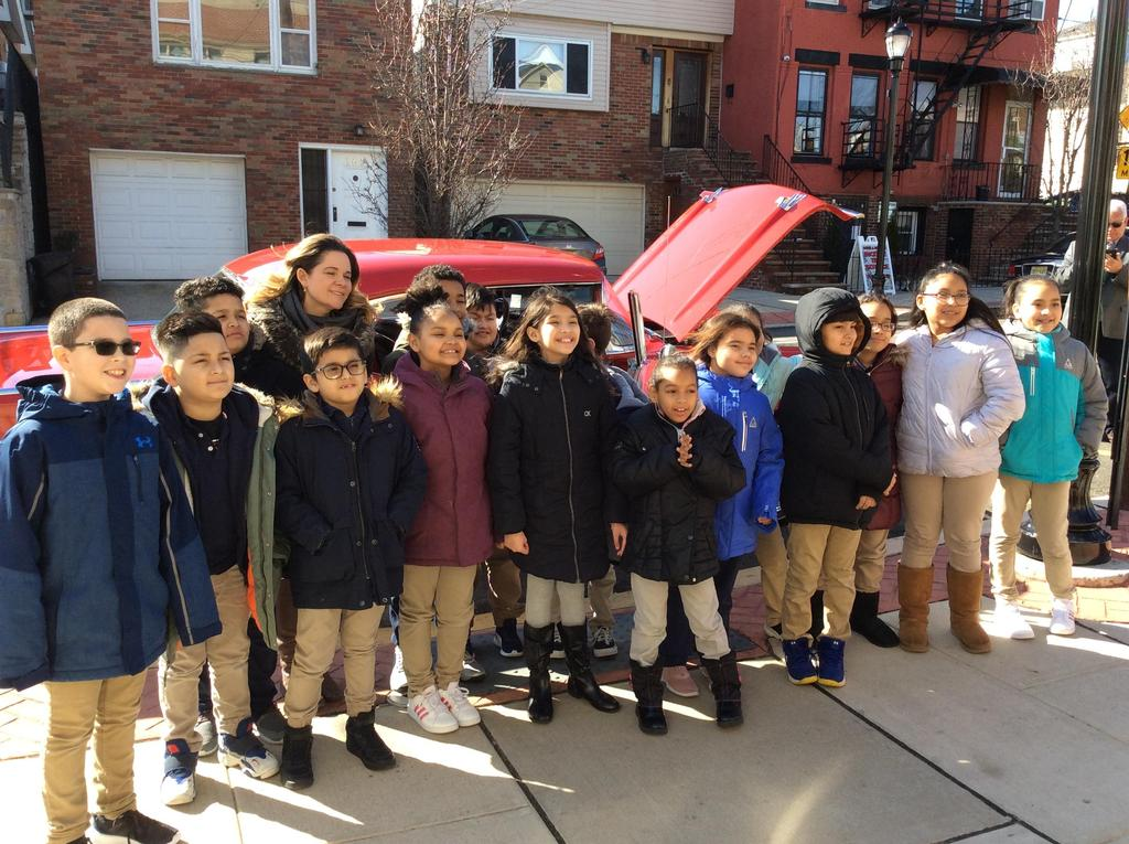 4th Grade class with teacher standing in front of the 57 Chevy