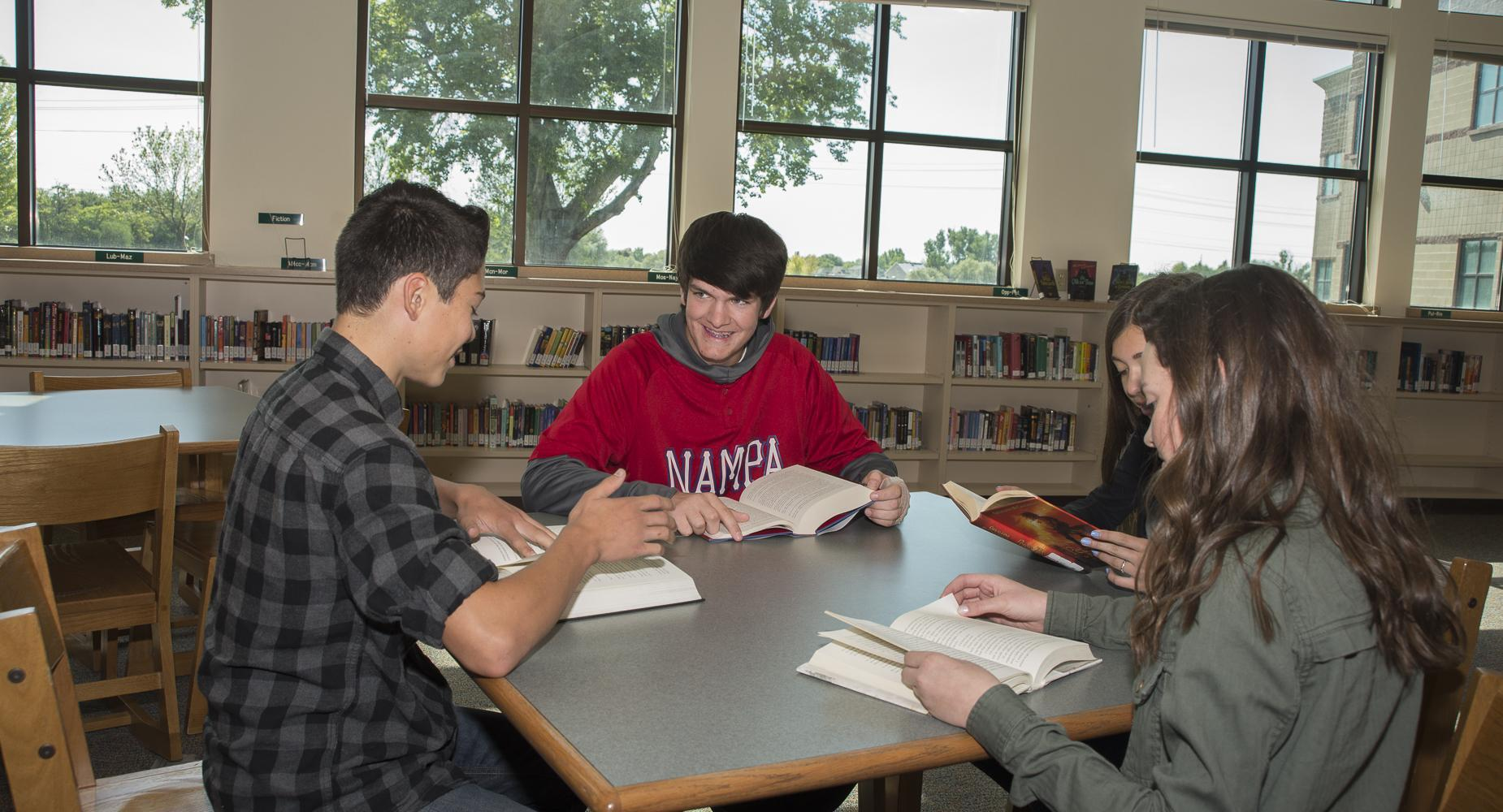 Students study at a table in the library