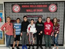 A woman standing next to 6 students in front of a black and white pattern with a Mineral Wells Junior High banner above them.