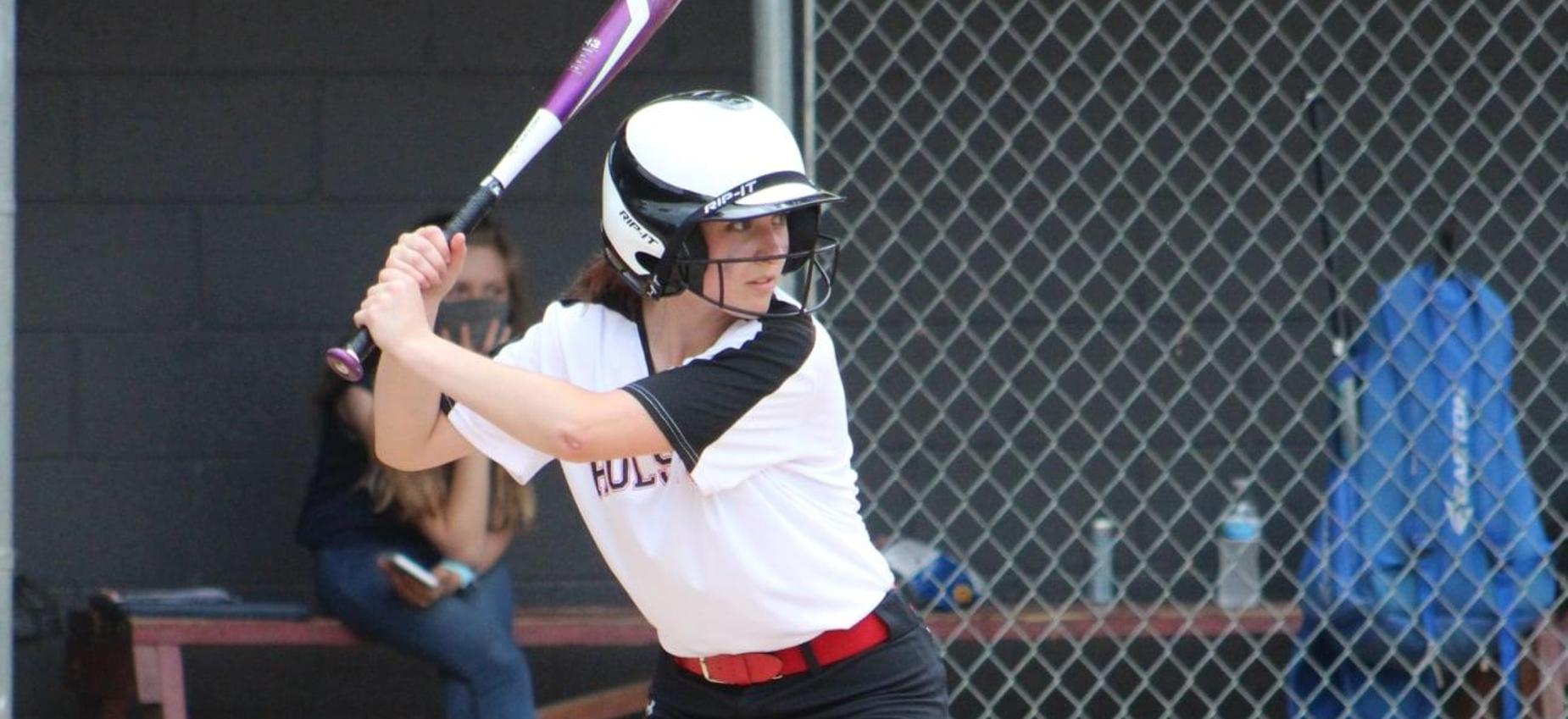 A softball player prepares to hit the ball.