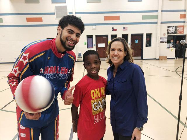 Sweet Lou of the Harlem Globetrotters poses with Clift Elementary student and teacher