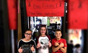 Three students with Ball electric sign