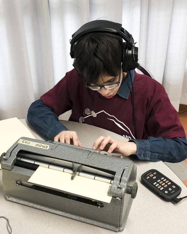A student being tested using a braillewriter and a Victor Stream