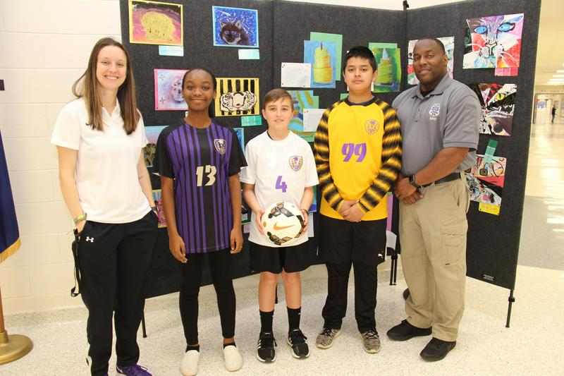 Pictured on the far left and far right are Batesburg-Leesville Middle School JV soccer team coaches Kayla Jennings and Charles Holloway.  Teammates Arden Etheredge, Hollis Ruff, and Felipe Diaz are seen showing off the team's new jerseys that were purchased thanks to collaborative fundraising efforts.