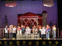 All of the Kindergarten students on Stage with five students holding the letters to spell BINGO.