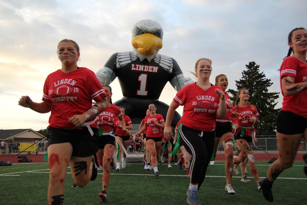 Powder puff football players running under an inflatable eagle onto a football field
