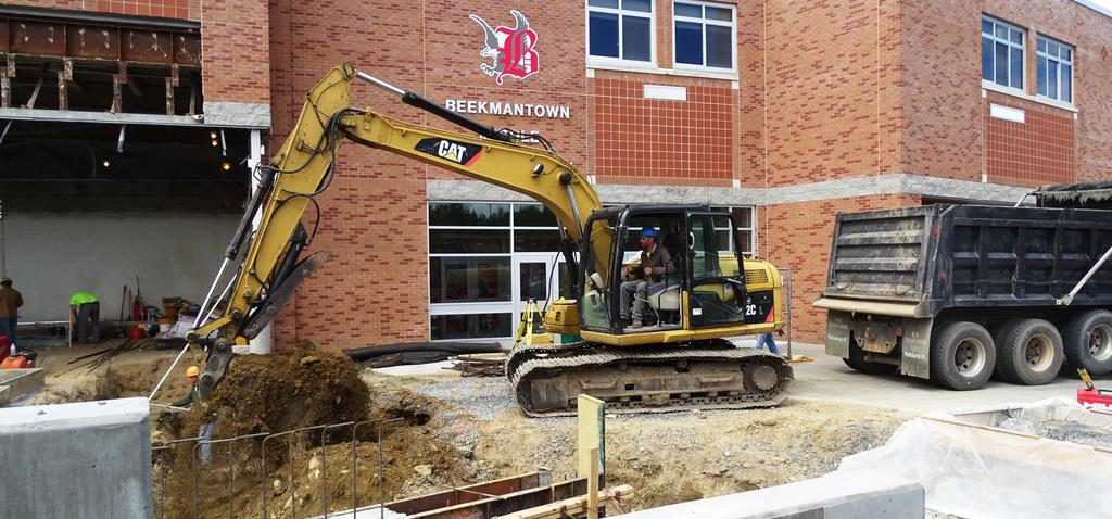 An excavator operator near the vestibule entrance to Beekmantown Middle School is excavating soil after regular school hours on Thursday, June 13, 2019. This job site will eventually become the Large Group Instruction Room, as part of this capital project's work scope for the construction season now underway.