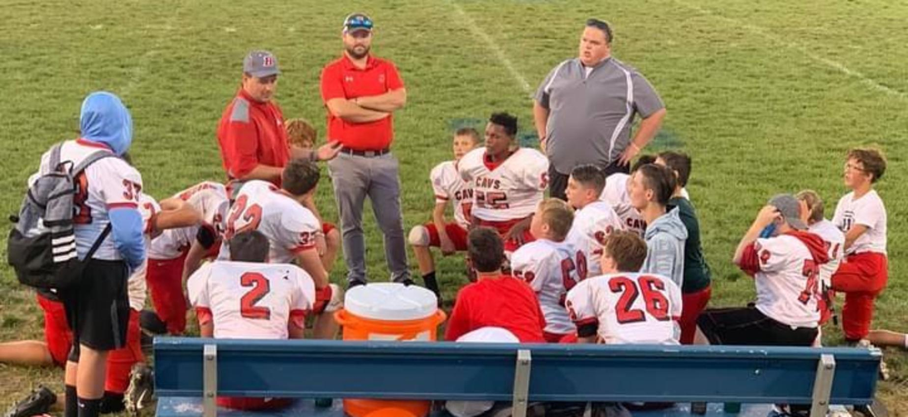 A coach talks to a group of football players on a field.