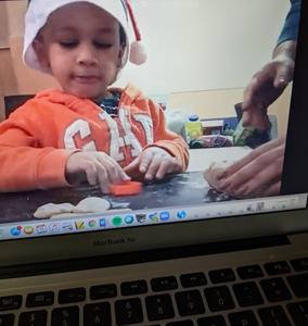 Boy cutting dough on zoom