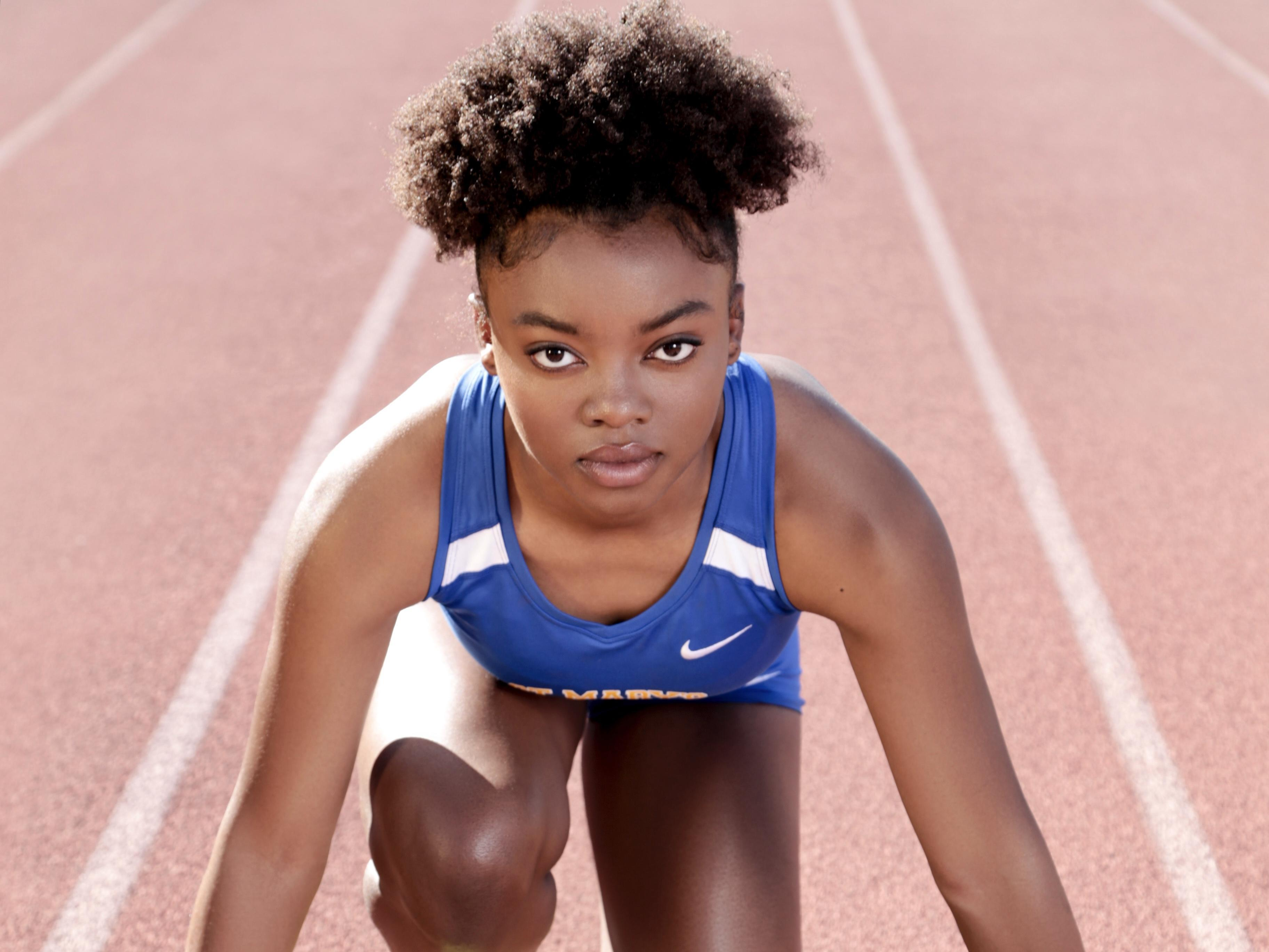 a student in track uniform posing on the track field
