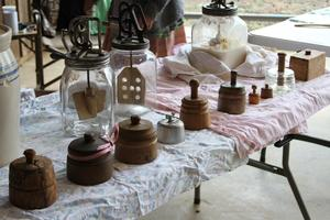 A variety of butter churners and containers at the butter churning demonstration table