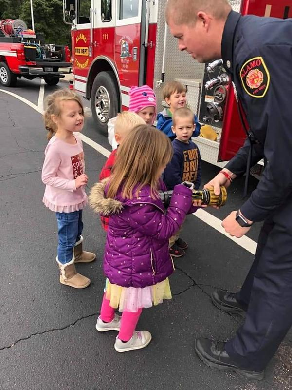 a firefighter shows students equipment on the truck.