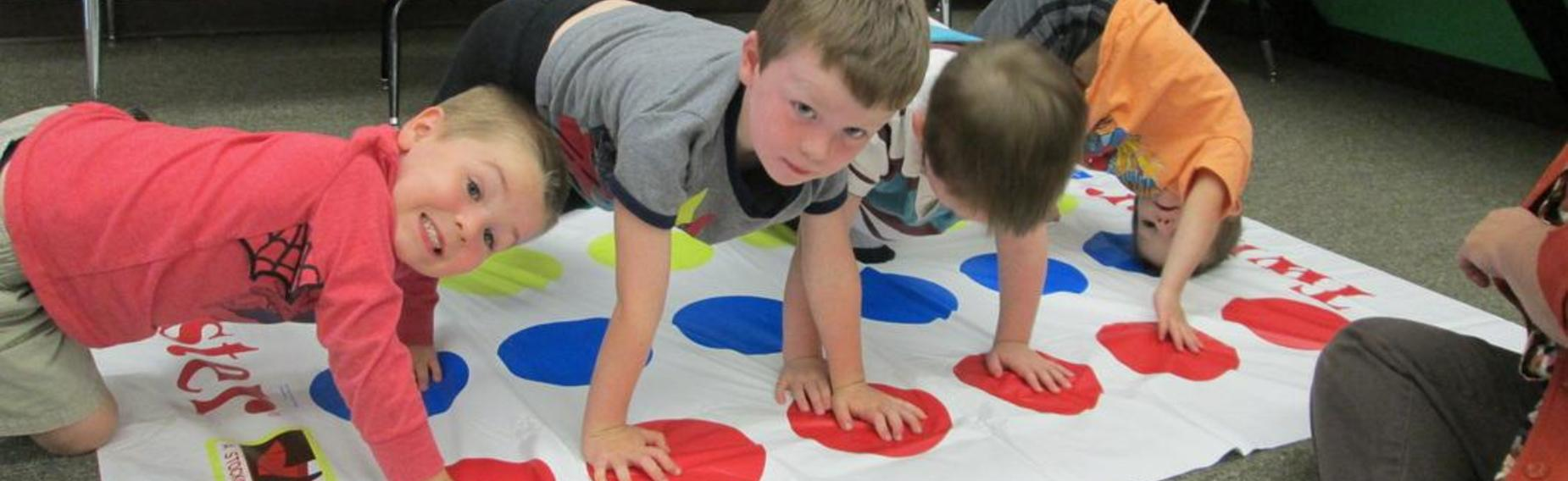 Four preschool children playing a game of Twister.