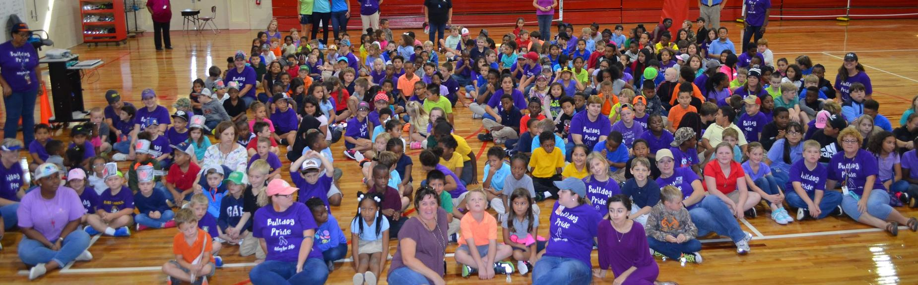 multiple classes of students sitting on floor in gym wearing purple shirts