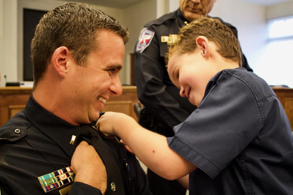 a boy pinning a police badge on his father