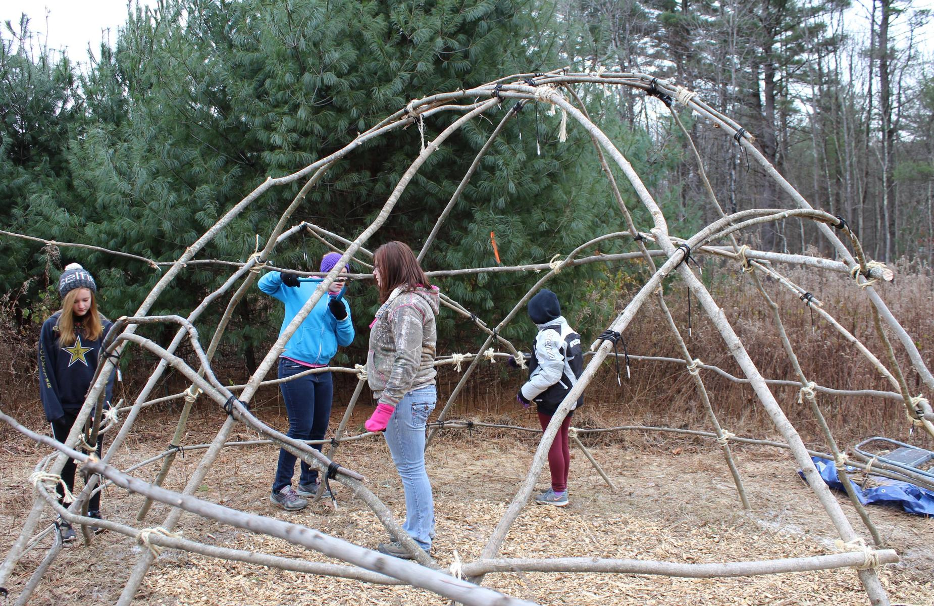 students building wigwam