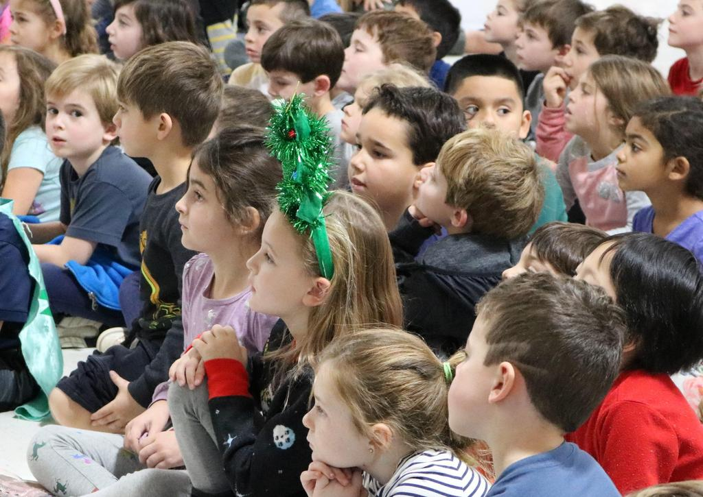 Photo of Lincoln preschoolers and kindergartners enjoying a holiday concert by visiting 5th graders from Wilson School.