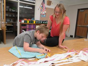 A third-grader concentrates while he sews the finishing work on an apron.