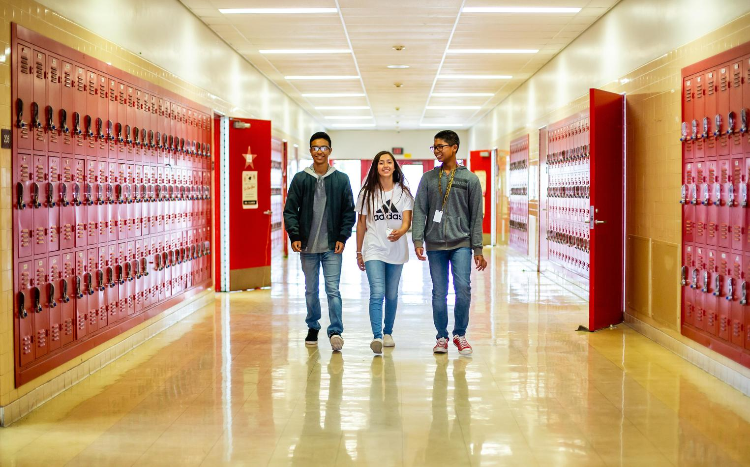 Three friends walking in hallway with rows of lockers.