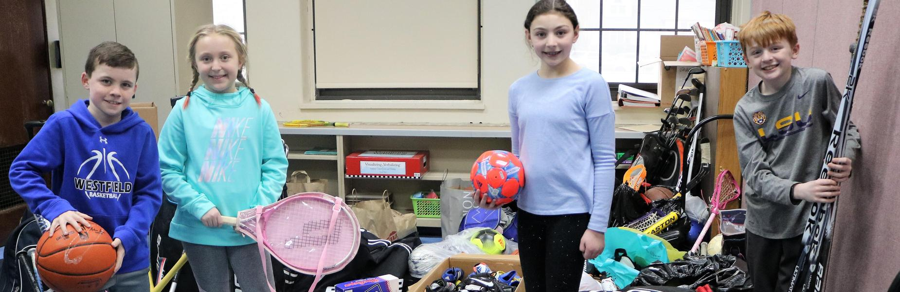Wilson 4th graders display gently used sporting equipment collected during the school's