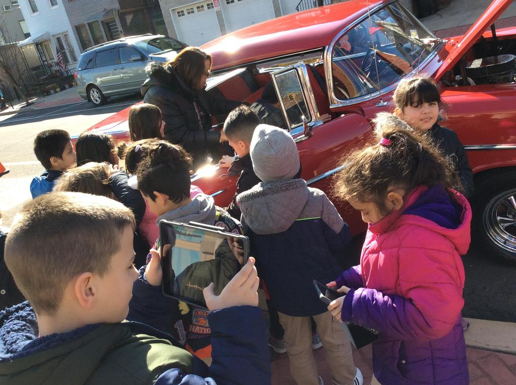 students holding ipad while looking at the 57 Chevy