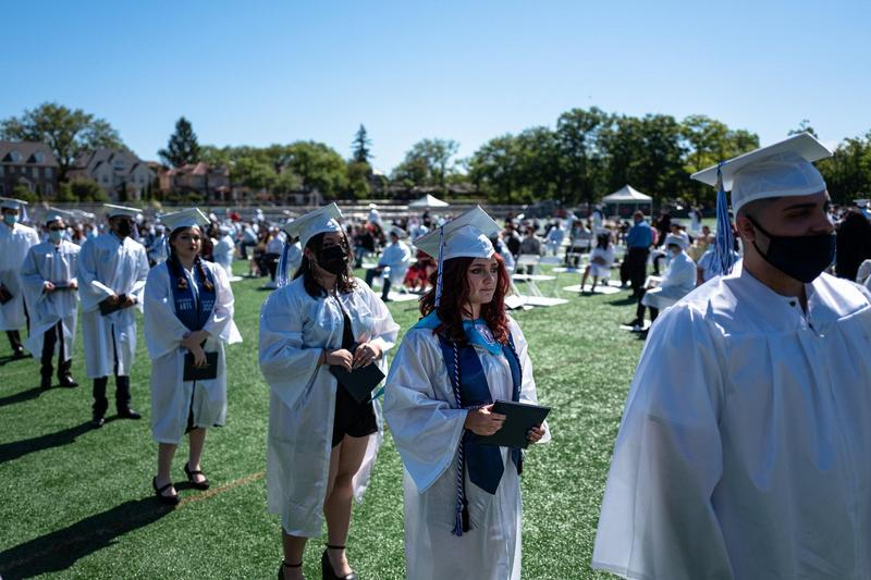 Fort Hamilton High School students walking at graduation in white robes