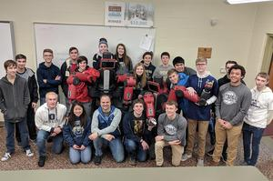 The entire computer science class poses for a picture next to the two robots.