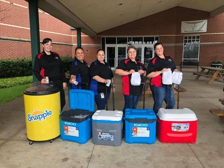 5 ladies with rolling coolers in matching uniform shirts