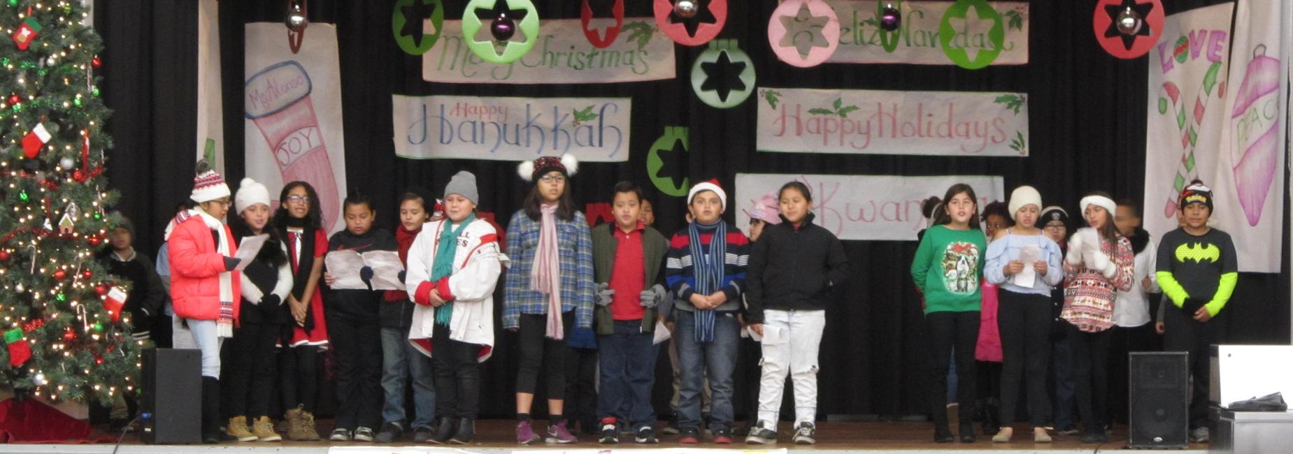 Students stand on stage during a Christmas performance.