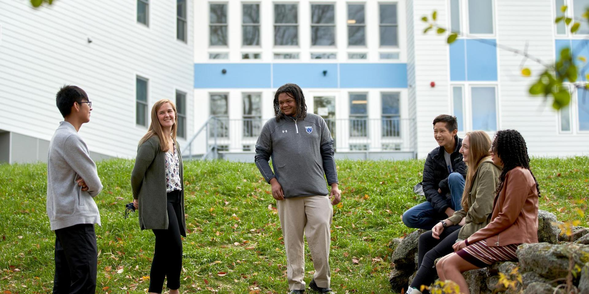 A group of students and faculty in front of the New Dorm.