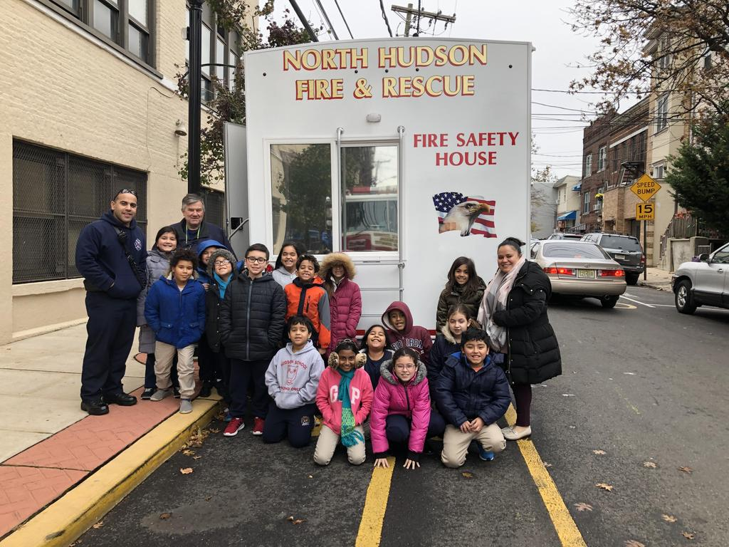 teachers with her class and the firemen in the back of the fire safety house