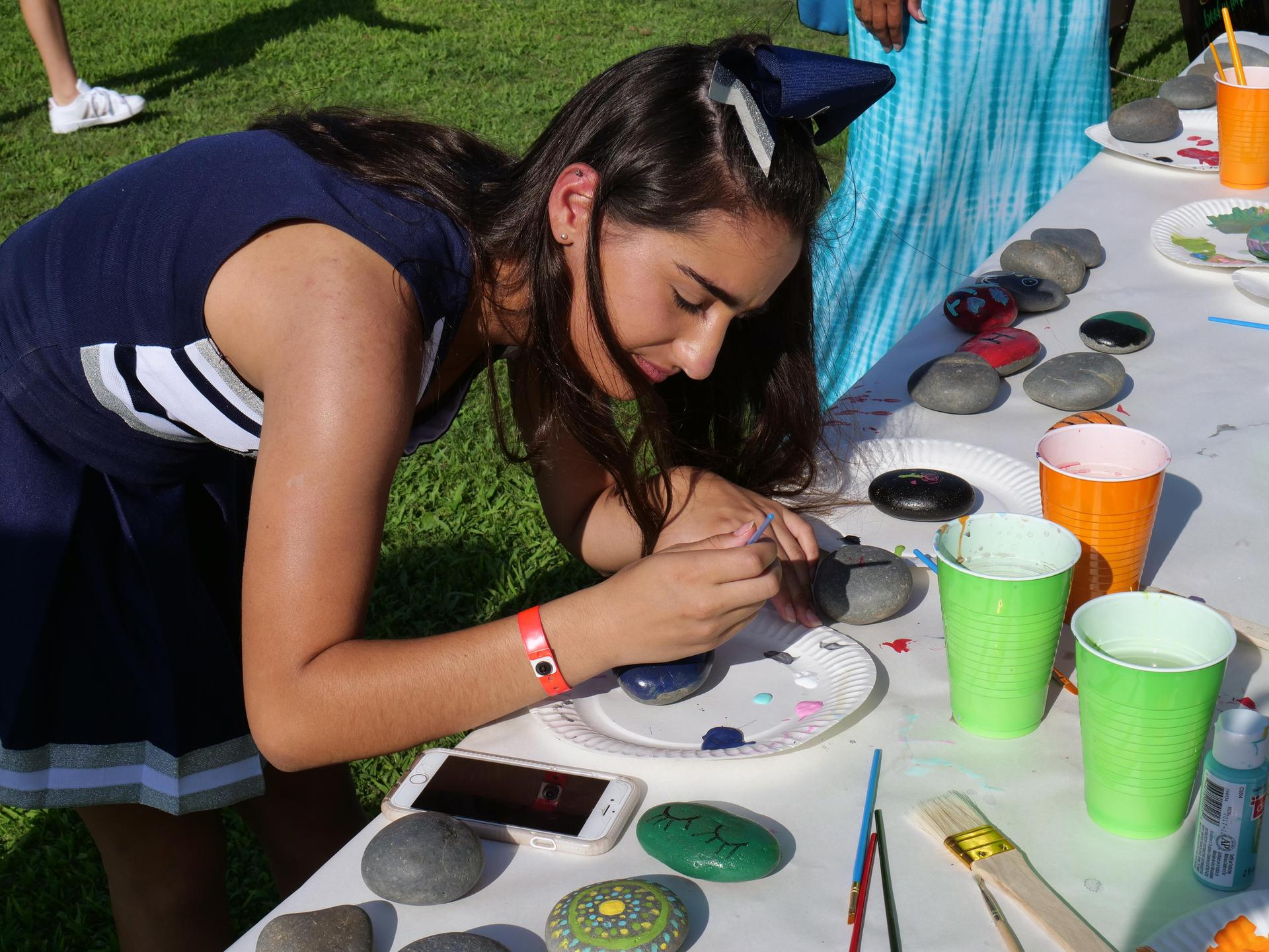 Senior cheerleader painting at the Husky Pride Picnic