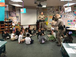 California Highway Patrol Officer reading to a group of students, image 5