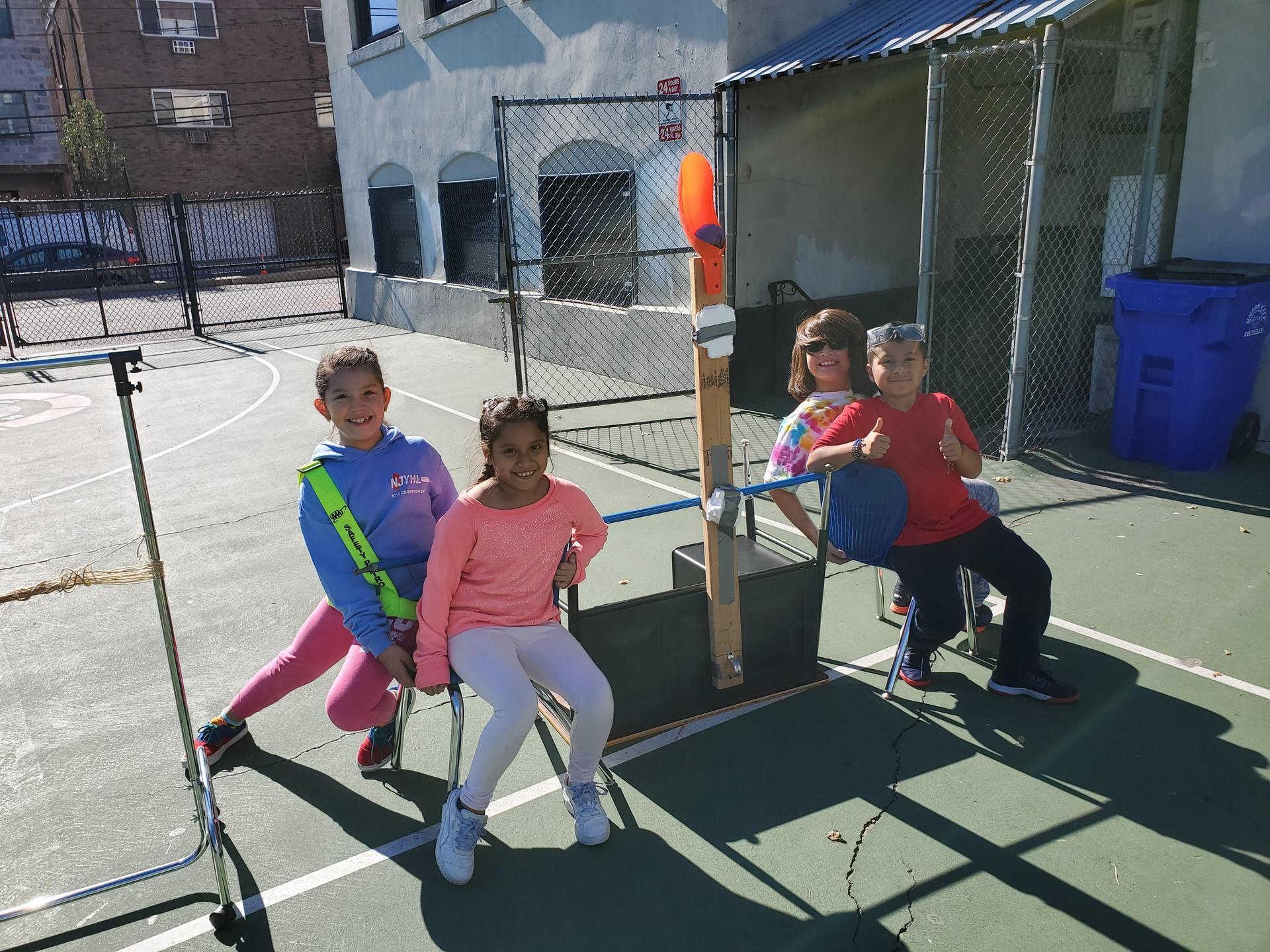 3rd grade students testing 2nd grade catapult design