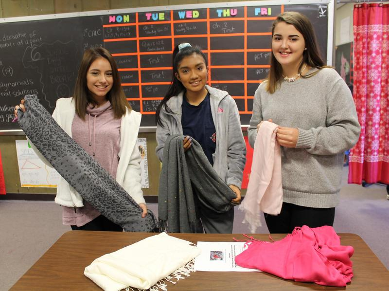 3 students from Mayfield High School organizing scarves for the
