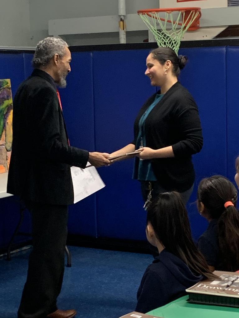 Artist Brooks handing over to the Art Teacher a plaque