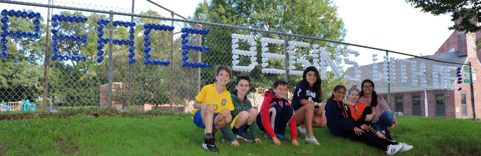 Franklin 5th graders pose in front of a sign in the fence created out of colorful plastic cups, saying