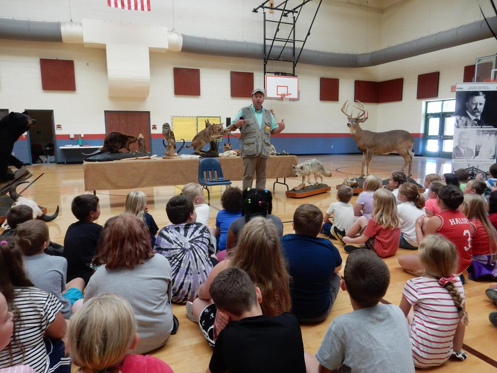 Representative from Ward Burton Wildlife shown with several mounted animal species, presenting info to students.