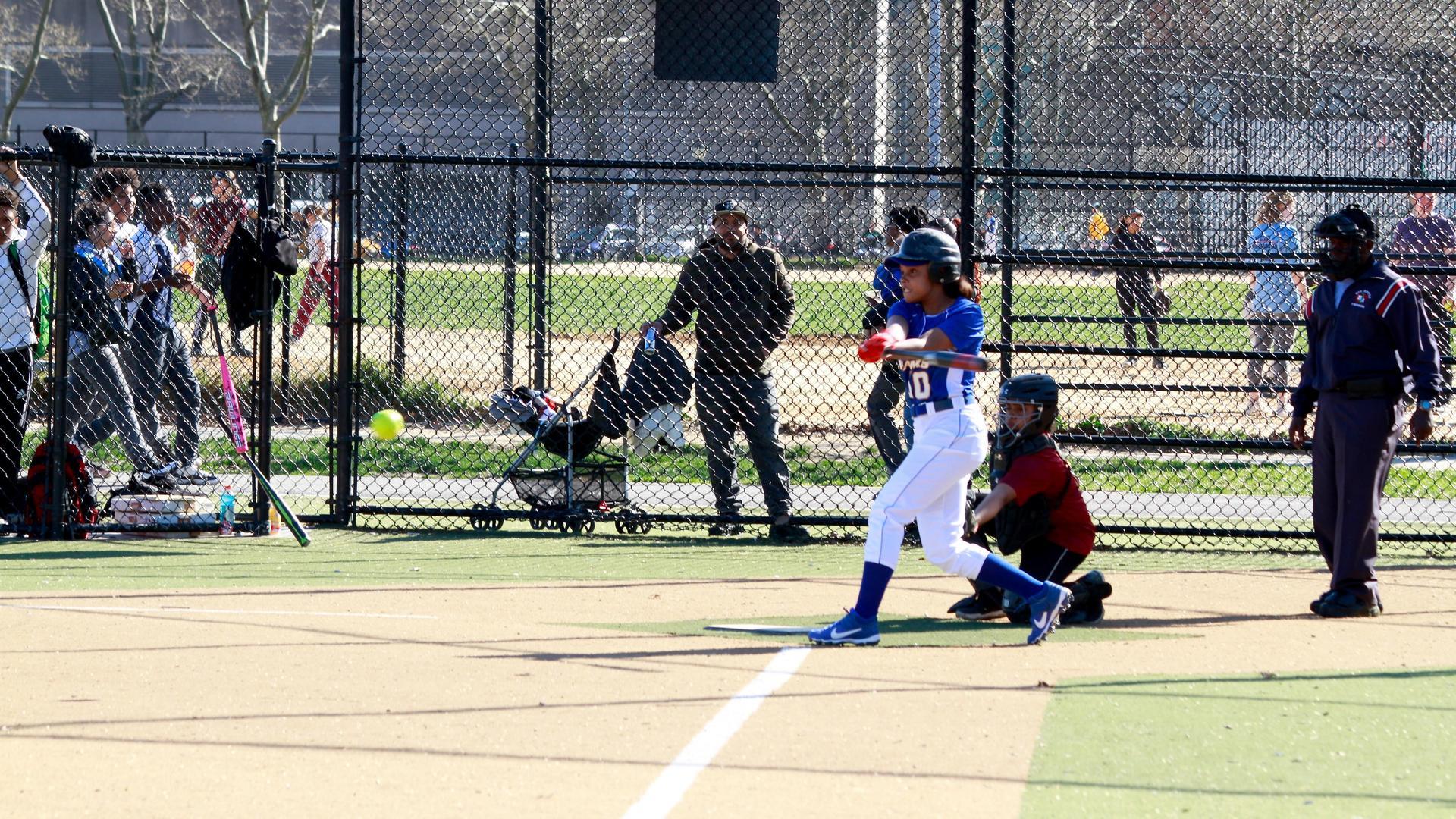 a girl hitting a softball with a bat.