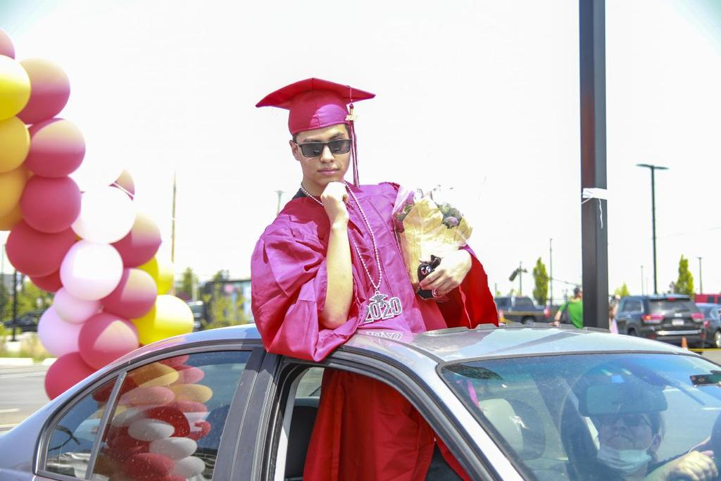 A grad standing through a sunroof