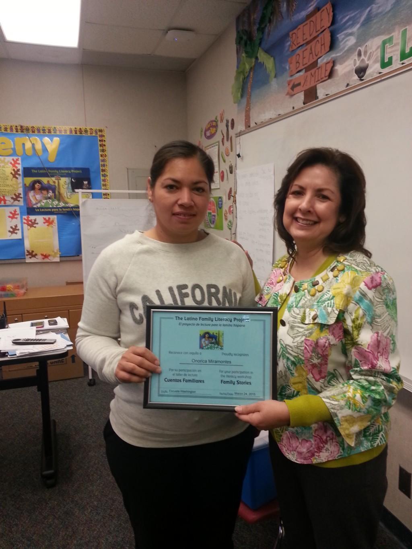 Parent receiving completion award on parent academy class