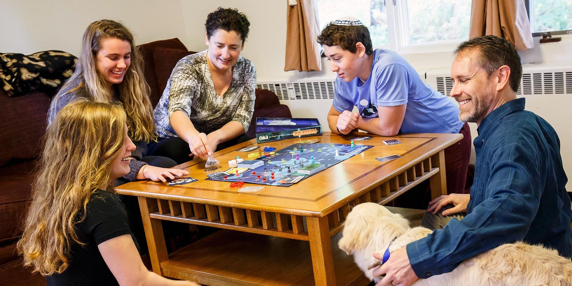 A group of students and adults playing a board game in a dorm.