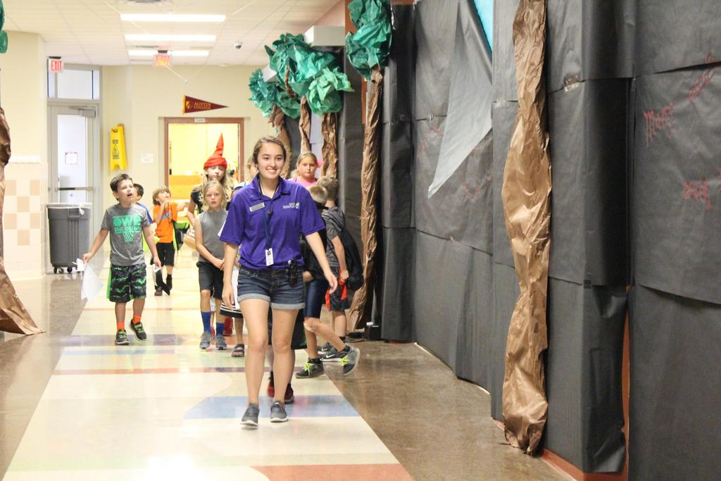 Camp counselor, Emily Claussen, leads Good Sam campers through the mythical-themed hallway for an afternoon activity.