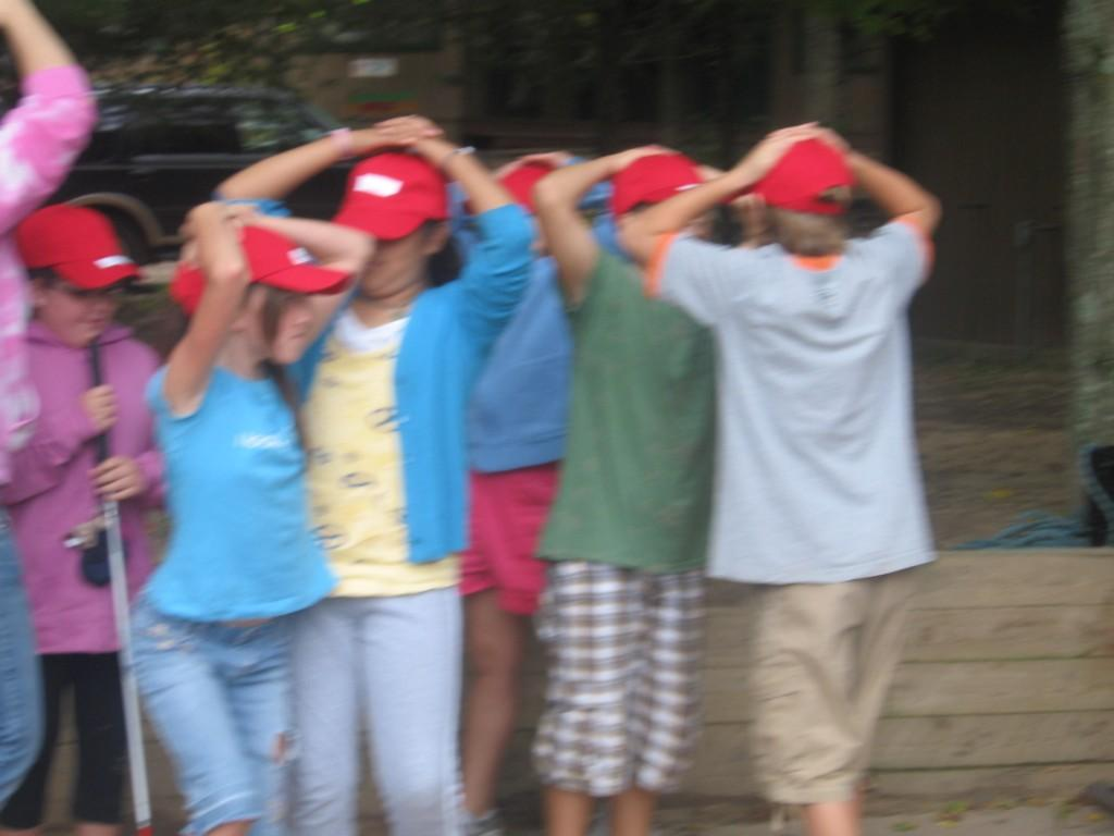 students with hands on their heads at camp