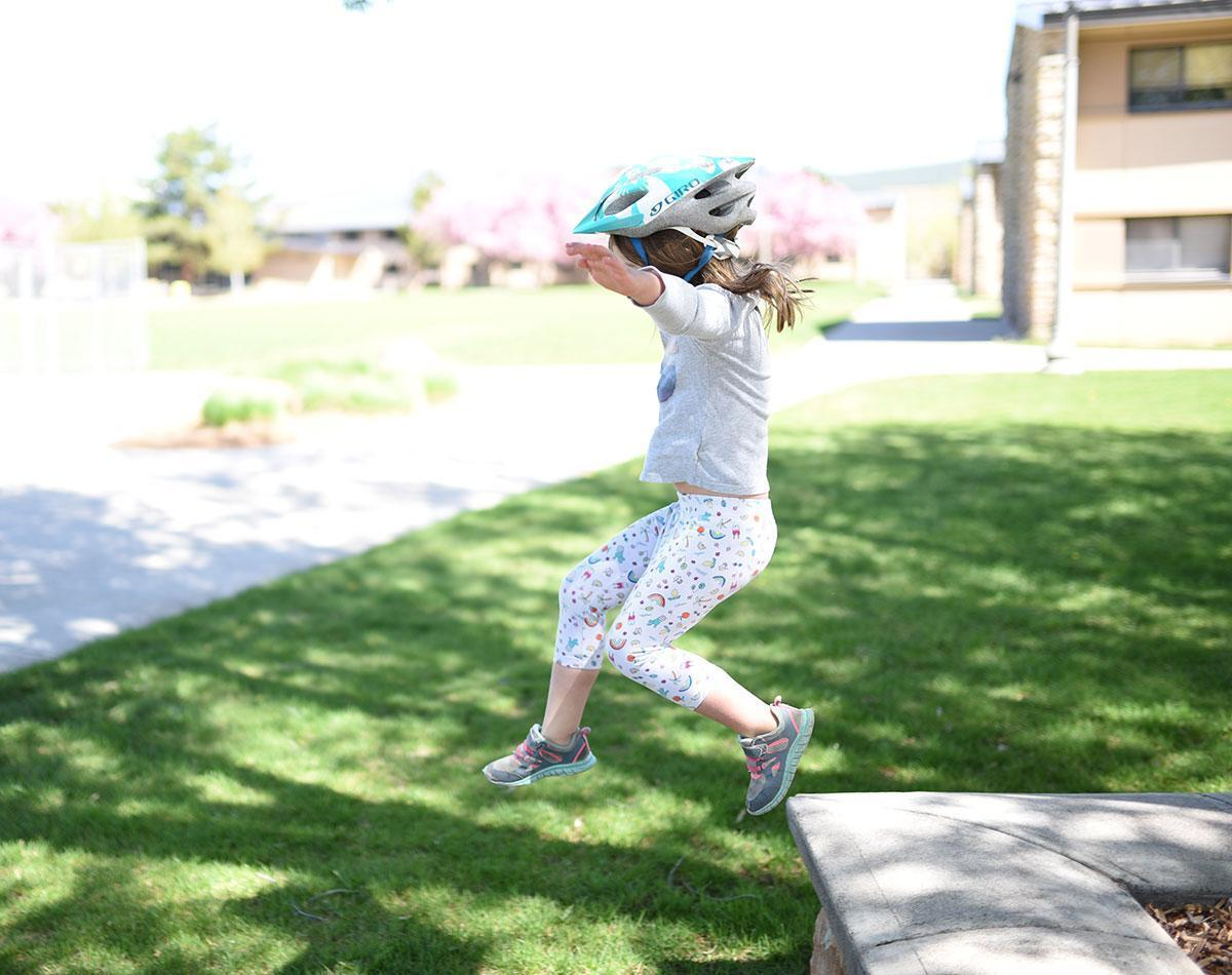 Child wearing a helmet jumping off a ledge